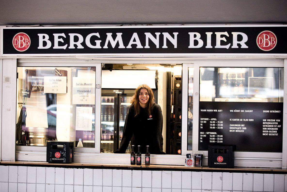 Mensch in schwarzem Kapuzenpulli im Bergmann Kiosk schaut aus dem Kiosk-Fenster